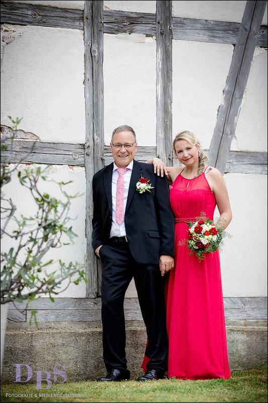 Brautpaar steht an einer Fachwerk Wand
