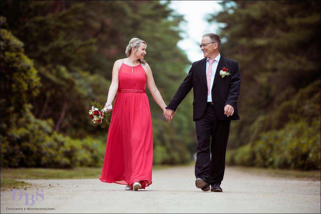 Brautpaar lachend laufend auf dem Weg