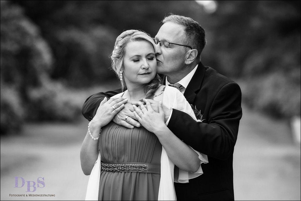 Brautpaar kuschelt mit Augen zu schwarz weiß Hochzeitsfoto