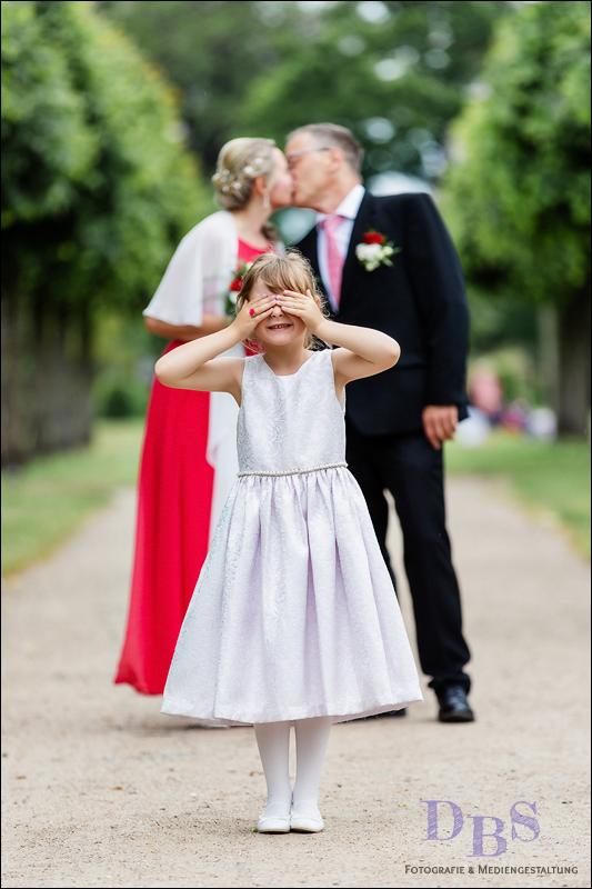 Brautpaar mit Tochter hält die Augen zu