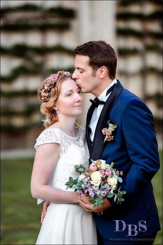 Brautpaar Hochzeitsbild Mann küsst Frau auf Stirn