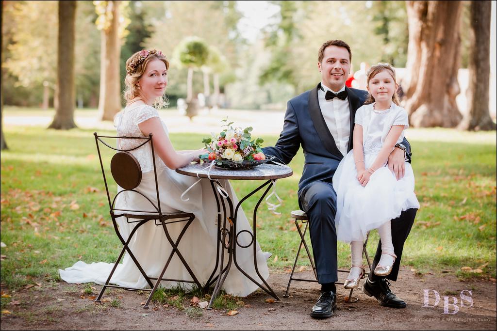 Brautpaar mit kleinem Mädchen Kind sitzt im Park